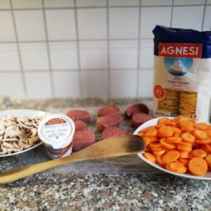 Kalbsmedaillons, geschnittene Champignons, Karotten und Teigwaren bereitgestellt