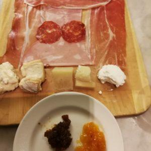 Platte angerichtet mit Parmaschinken, verschiedenen Käse und süss-sauer Saucen