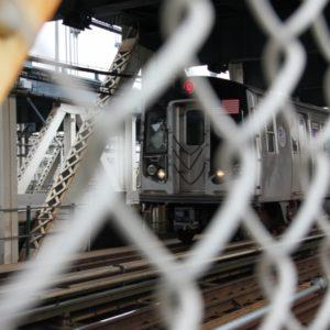 U-Bahn in Fahrt - mit Maschendraht im Vordergrund