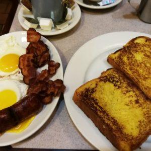 Amerikanisches Frühstück mit goldgelb gebratenem Toast, separat 2 Spiegeleier mit gebratenem Speck und Würstchen