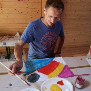 Dani beim Malen seines Bild in den Farben blau, rot, grün und violett