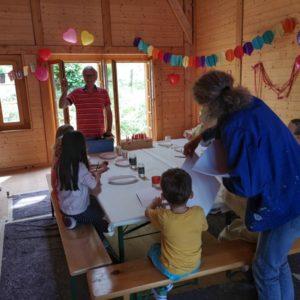 Beginn Malparty mit Verteilung der Pinsel und Papier an die Kinder