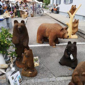 geschnitzte Bären gross in Braun, im Hintergrund Stände mit vielen Besuchern