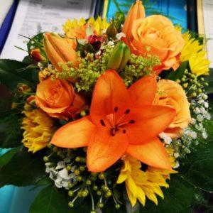 Geburtstagsstrauss mit Rosen und Lilien in Orange und Sonnenblumen mit grünem Dekor
