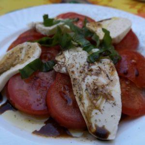 Tomatensalat mit Mozzarellascheiben, dekoriert mit frischem Basilikum