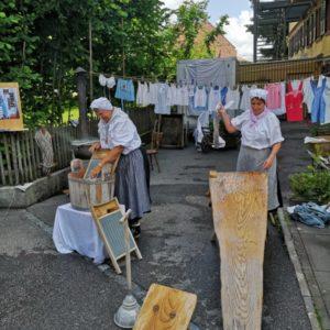 Waschfrauen im Einsatz - Am Waschzuber und eine am Wäsche klopfen mit aufgehängter Wäsche im Hintergrund