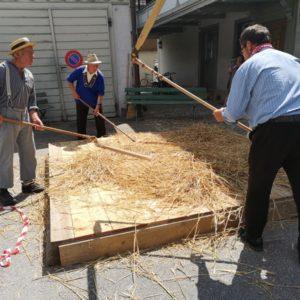 Drescher in alter Kleidung zu dritt am Bearbeiten von Weizen
