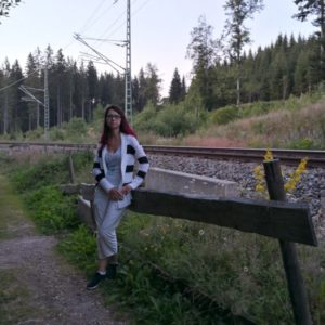 Alex posierend am Holzhag vor Bahnlinie in heller Hose und schwarzweisser Jacke
