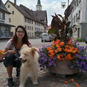 Alex in weissem Shirt und schwarzer 3/4 - Hose mit Viktor (nicht in Kamera schauend) neben Blumentrog mit violetten und orangen Blumen kniend