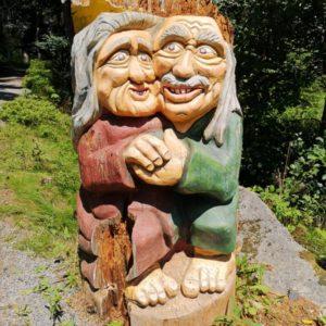 Holzskulptur als altes Ehepaar sich umarmend mit grossen Augen, grauen langen Haaren und lächelnd