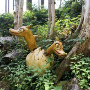 zwei schlüpfende Drachen in gelb mit grünen Punkten aus hellgelbem Ei schlüpfend aus Holz geschnitzt am bemoosten Waldboden