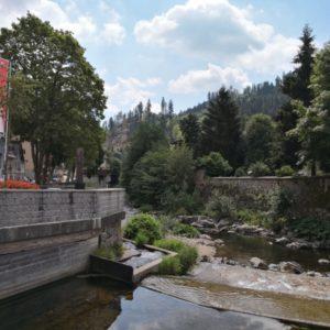 Blick auf Bachlauf mit Bachtreppe und linkerhand graue Mauer mit Baeumen gesaeumt undd Fahne in rot-weiss
