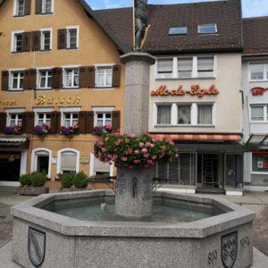 Grau-marmorierter Brunnen mit Geranien in rosa und obendrauf Statue in grün-gold