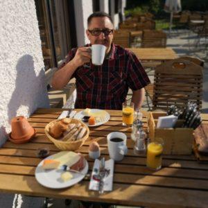 gedeckte Frühstücktafel auf Terrasse mit Kaffee, Brötchen und O-Saft