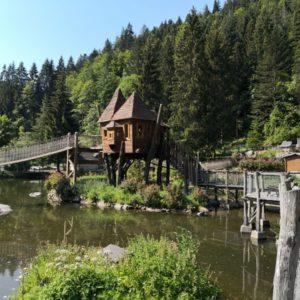 Holzbruecke mit Haeuschen mgeben von gruenlichem Teich