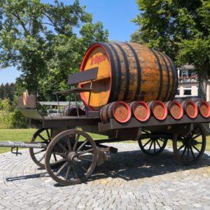 Alter Wagen in dunkelbraun mit grossem Rothaus-Holzfass und an den Seiten sieben kleinen Holzfässern alle in hellbraun mit rotem Reifen