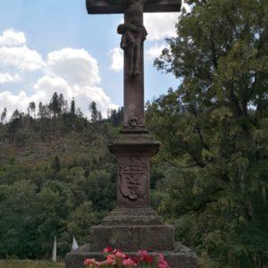 Steinkreuz mit Jesus und im Vordergrund rosa Geranien