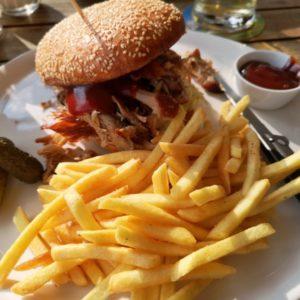Burger aus Pulled Pork mit Barbecuesauce nappiert, als Beilage Pommes Frites und Deko Essigguerkli