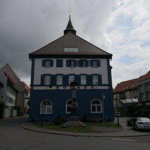 Rathaus mit blau-weisser Front, im Vordergrund Hauptstrasse
