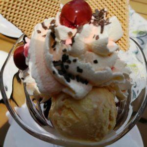 Eisbecher mit Vanille-Eis, Kirschen und Rahm dekoriert