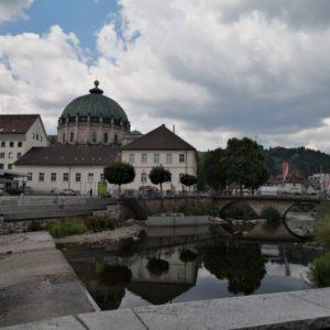 Blick zum Dom, im Vorderrund weisse Schulgebaeude und Dorfbach