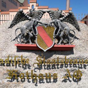 Stein mt Wappen in Rot-gold und zwei grauen Adlern sowie dem Rothaus Brauerei Schriftzug in Gold