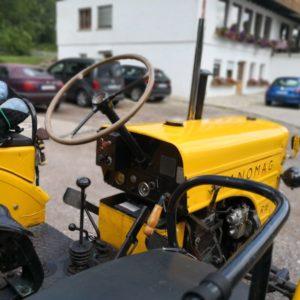 Oltimer Traktor in gelb von Seite mit Blick auf Lenkrad und Schaltknüppel