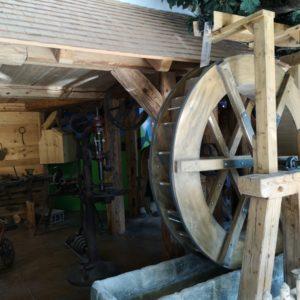 Drehendes Wasserrad aus hellem Holz, im Hintergrund alte Schmiede