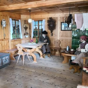 Bauernstube mit Mann sitzend vor Weinflasche, waehrend Frau am Ofen in grün strickt