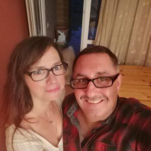 Selfie im Wohnzimmer vor weinroter Wand und hellbraunem Holztisch