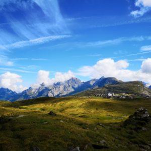 Blick auf Bergkette bei blauem Himmel, im Vordergrund gruene Wiesen