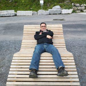 Mario liegend auf Riesenliegestuhl aus hellem Holz
